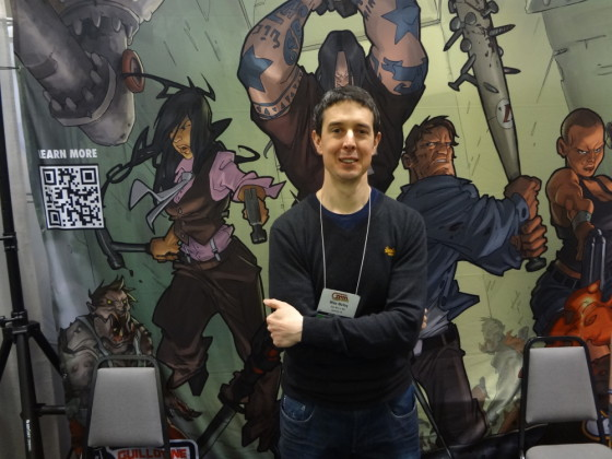 Thin British painter Mike McVey with crossed arms in front of Zombicide poster at Cool Mini booth