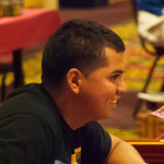 Closeup of Heroclix player Justin Jimenez smiling at a tournament table