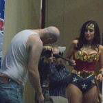 Valerie Perez dressed as Wonder Woman fends off Zombie with a baton on stage at Las Vegas Comic Expo