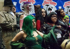 Green-clad Anne Marie Page cosplays as Rydia from her wheelchair with a female Frieza and Edna E. Mode behind her at Las Vegas Comic Expo Cosplay Contest