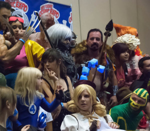 Cosplayers gathered on stage with a variety of costumes including Mami Kraven and Invisible Woman